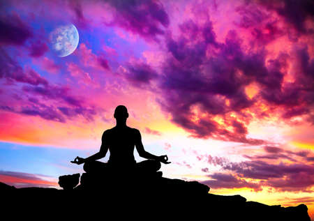 Yoga meditation in lotus pose by man silhouette with moon and purple dramatic sunset sky background. Free space for text and can be used as template for web-site photo
