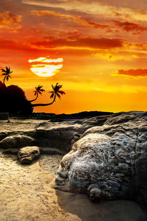rest in peace: Stone Shiva face on the Vagator beach at orange sunset sky and palm silhouettes in Goa, India