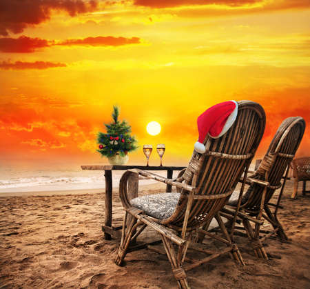 Christmas tree, Two glasses of champagne and Christmas hat on the chair on the beach with view to the ocean  and orange sunset sky in Goa, India photo