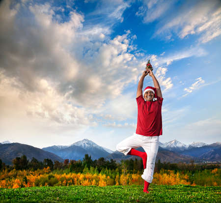 Christmas yoga vrikshasana tree pose by happy Indian man in white trousers, red socks and Christmas hat with Christmas tree at mountain background. Free space for text photo
