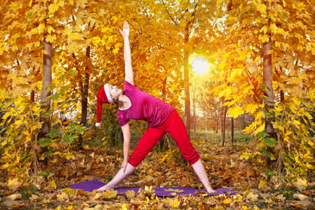 Christmas Yoga trikonasana triangle pose by beautiful woman in red cloth and yellow leaves around at sunset background photo