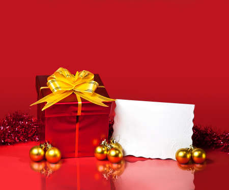 Christmas gift box of red color with Christmas golden balls and blank card at red background. Free space for your text  photo