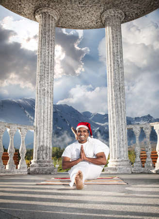 Christmas yoga eka pada shirshasana pose by happy Indian man in white costume and Christmas hat at snow mountain background.  photo