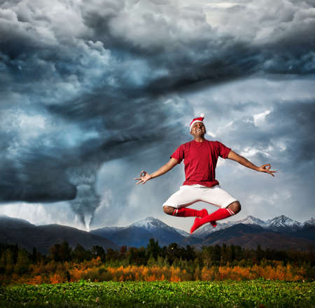 Flying Indian man in meditation in Christmas hat at Hurricane and dramatic sky background. Represent negotiation of your inner fears photo