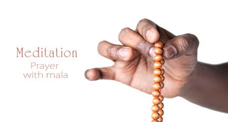 Hand holding japa mala beads for prayer by Indian man isolated at white background. Free space for your text photo