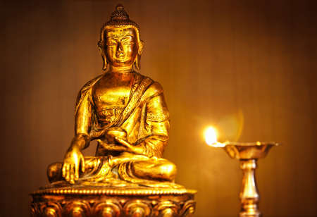 Golden Buddha statue on altar with oil lamp with flame  Stock Photo