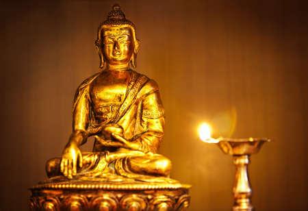 candil: Oro estatua de Buda en el altar con la lámpara de aceite con la llama