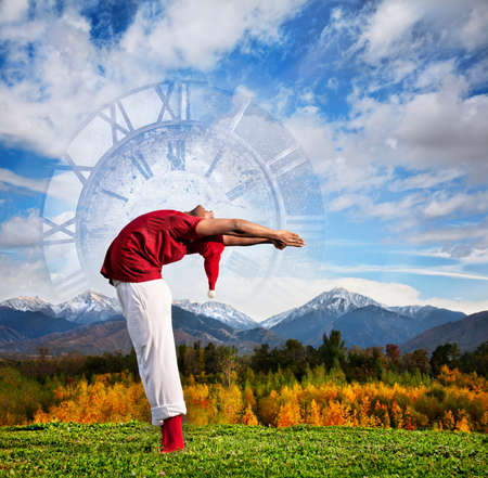 Christmas yoga Hasta Uttanasana backward bending pose by Indian man in white trousers, red socks and Christmas hat at clock and nature background photo