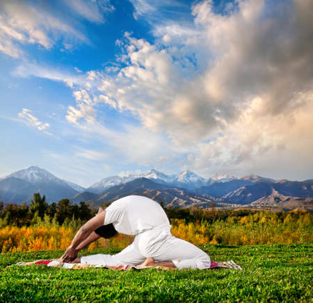backward: Yoga valakhilyasana backward bending pose by Indian Man in white cloth in the morning at mountain and cloudy sky background