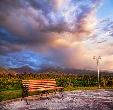 Lonely bench in the park with lamppost nearby at mountain and sunset dramatic sky background. Presidents park in Almaty, Kazakhstan