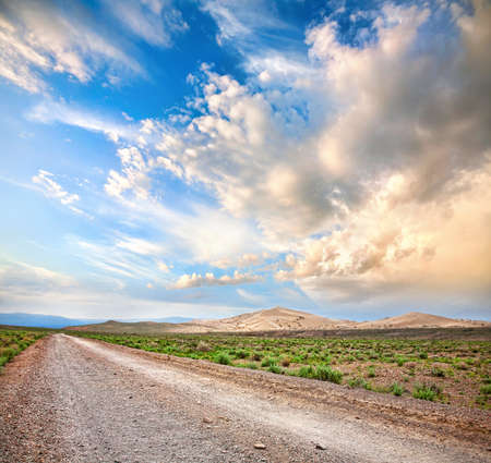 Road to the mountains through the desert at dramatic cloudy sky background photo
