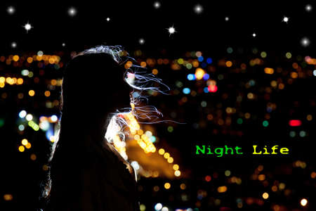 Woman portrait in silhouette with hair waving in the breeze at night city background. Free space for your text photo