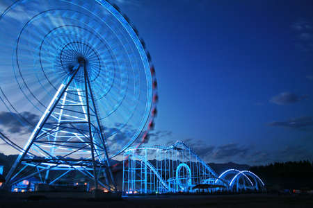 kyrgyzstan: glowing Observation wheel and rollercoaster at mountain and evening sky background in Issyk-Kul lake, Kyrgyzstan Stock Photo