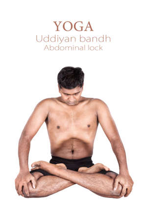 padmasana: Yoga uddiyan bandha abdominal lock in lotus pose by Indian man isolated at white background. Free space for text and can be used as template for web-site Stock Photo