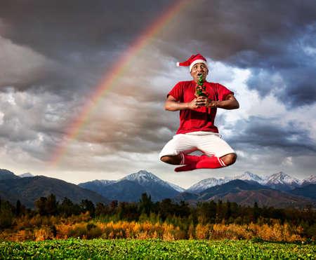 Saltando por el yoga indio en padmasana loto con el árbol de Navidad en pantalón blanco, medias rojas y un sombrero de Navidad en el cielo, las montañas y dramática con el arco iris de fondo