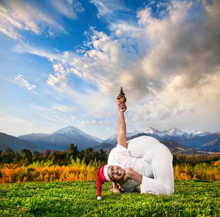 Yoga bal krishnasana pose by Indian man with Christmas tree in white cloth and Christmas hat at mountain background photo