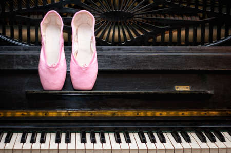 ballet slippers: Pink pointe on the black old piano