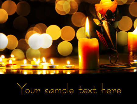 Lighting candles with flame at bokeh background. Space for your text photo