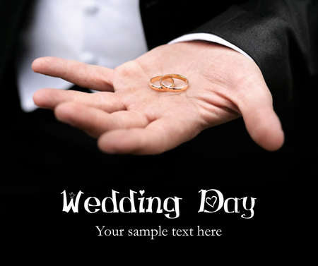 Groom holding two wedding rings on his hand close up at black background. Free space for your text and can be used as template for web design and magazine photo