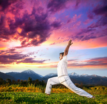 Yoga virabhadrasana I warrior pose by Indian Man in white cloth in the morning at mountain background photo