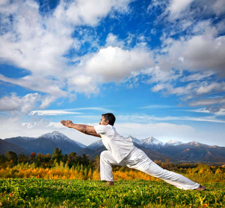 pilates man: Yoga virabhadrasana warrior pose by Indian Man in white cloth in the morning at mountain background Stock Photo