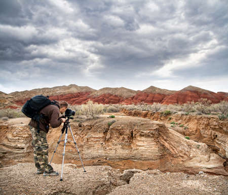 Photographer shooting drought Aktau mountains at dramatic sky background in altyn emel national park in Kazakhstan Stock Photo - 11763450