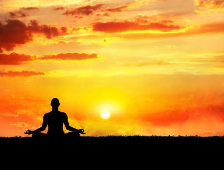 Yoga meditation in lotus pose by man silhouette at sunset sky background. Free space for text and can be used as template for web-site
