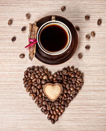 granos de cafe: Taza de caf� y granos en forma de coraz�n con la galleta en ella y la corteza de canela envuelto con cinta roja sobre el plato. Fondo de color marr�n con textura. Representar a d�a de San Valent�n