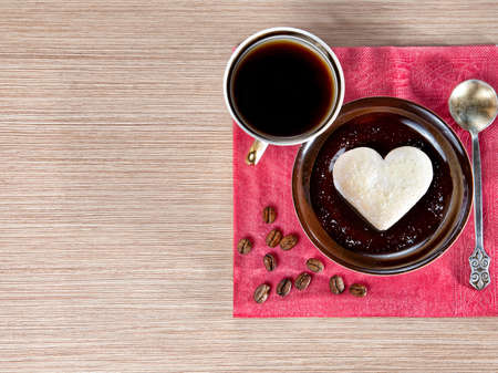 Cup of Coffee and cookie in shape of heart on the brown saucer. Grains and golden spoon laying on the red napkin near by on the table. Represent Valentines day. Free space for your text photo
