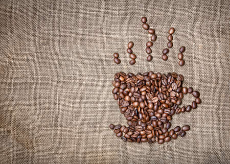 cofee: Cup of coffee with steam made from coffee beans on textured brown sack. Free space for your text