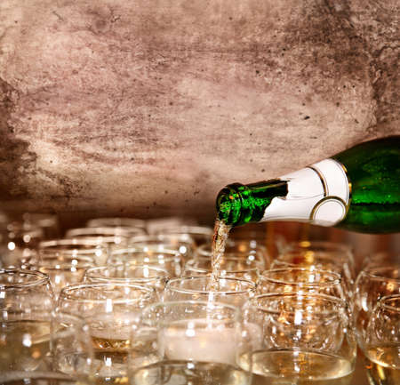 Pouring Champagne to the glasses in restaurant at vintage textured background. Represents party. Free space for your text