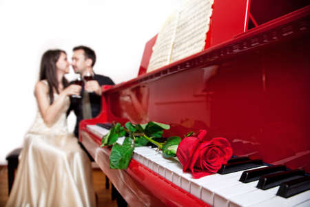 Rote Rose auf der roten Tastatur eines Flügels im Fokus und Paar sitzt auf dem Stuhl mit Gläser Wein am Hintergrund