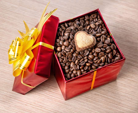 Coffee grains with heart shape cookie in Red box with yellow ribbon on the table. Respresent Valentines day photo