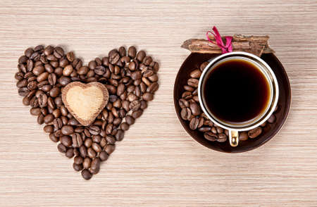 granos de cafe: Taza de caf� y granos en forma de coraz�n con la galleta en la corteza de canela y envuelto con cinta roja sobre el plato. Representan D�a de San Valent�n