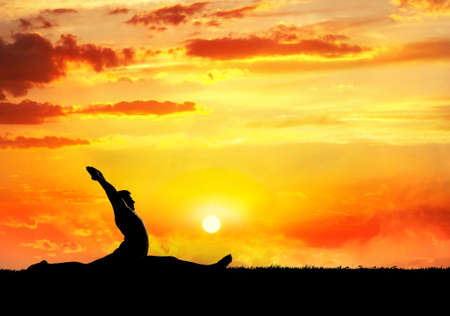 Yoga hanumanasana monkey pose by man silhouette at sunset sky background. Free space for text and can be used as template for web-site photo