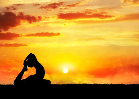 Yoga raja kapotasana pigeon pose by man silhouette at sunset sky background. photo