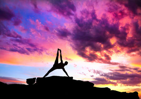 yoga sunset: Yoga Vasisthasana plank balancing pose by Man in silhouette on the rock outdoors at mountains and cloudy sky background