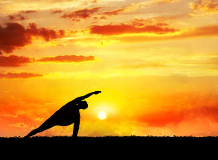 Yoga utthita parsvakonasana horizon pose by man silhouette at sunset sky background. Free space for text and can be used as template for web-site photo