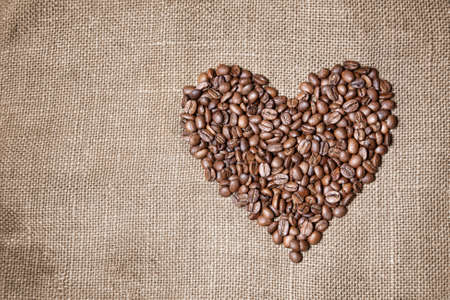 Heart made from coffee beans on textured brown sack. Free space for your text photo