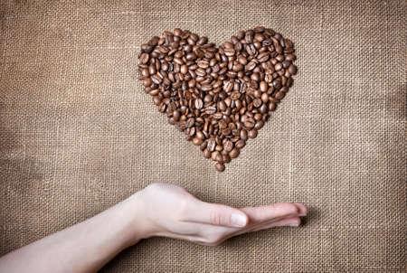 granos de cafe: Corazón de granos de café y de la mujer en la mano por debajo de saco marrón con textura