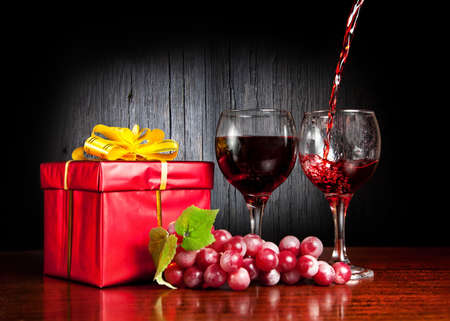 wine gift: Two glasses with wine, grapes and red present with yellow bow. Wine pouring to the glass at textured wooden background