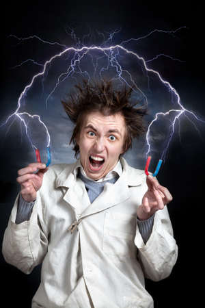 Crazy young professor with magnets in white coat. Thunder strikes from magnets around him photo