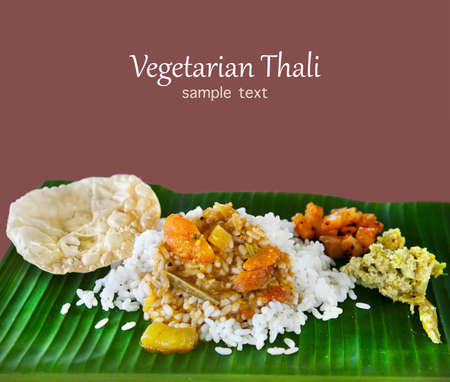 veg: Indian traditional vegetarian thali from rice, sambar, cucumber, potatoes, pickle and puri on banana leaf at brown background.  Stock Photo