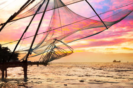 chinese fishing nets: Chinese Fishing nets and small ship at dramatic sunset sky background in Kochi, Kerala, India