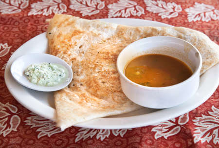 dosa: Indian traditional vegetarian masala dosa with potato inside, sambar and coconut chutney nearby at Indian restaurant