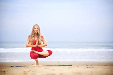 baddha: Yoga Ardha Baddha Padma Padangusthasana balancing on toes by young woman with long hair in red cloth on the beach at ocean background  Stock Photo