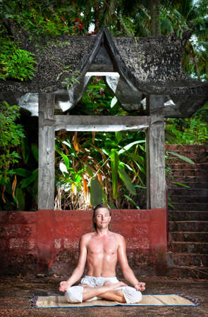Yoga meditation in lotus pose by man in white trousers at stone templa background in tropical forest  photo