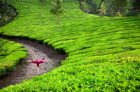 Yoga virabhadrasana III warrior pose by woman in red cloth on tea plantations in Munnar hills, Kerala, India Stok Fotoğraf