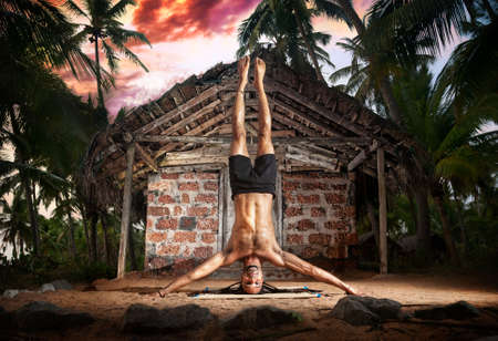 Yoga mukta hasta shirshasana, head stand pose by fit man with dreadlocks on the beach near the fishermen hut in Varkala, Kerala, India photo