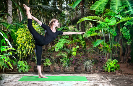 tree position: Yoga Natarajasana dancer balancing pose by woman in black cloth in the garden with palms, banana trees and plants in the pots Stock Photo